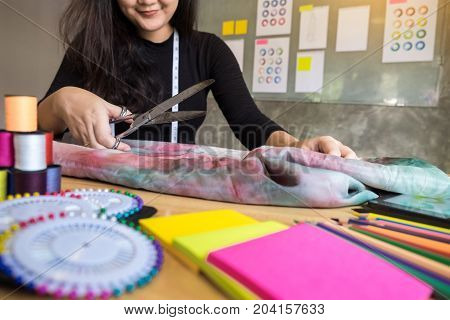 Hands notch tailor tailor's scissors cloth cutting a piece of fabric (fashion designer concept)