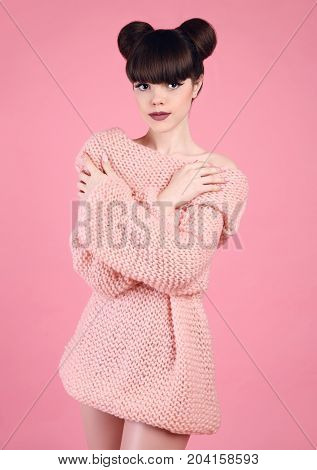 Fashion studio teen look style over pink. Fashionable young girl wears wool knitting sweater. Brunette with matte lips and bun hairstyle in soft pullover posing isolated on studio background.