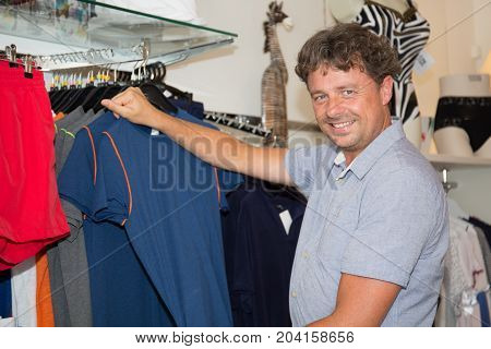 Handsome Cheerful Man Choosing Clothes In A Shop