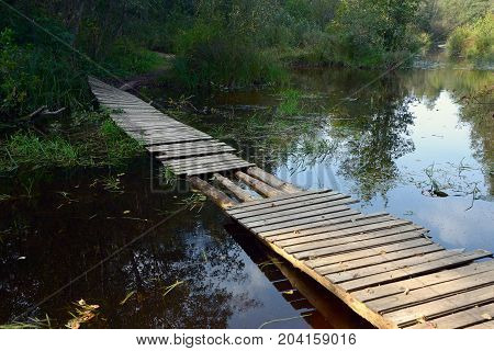 Od wooden bridge across the old river