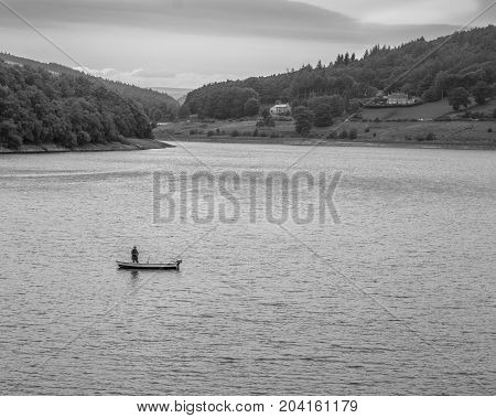 Lone fly fisherman on Ladybower Reservoir. Fly fisherman in a small lake boat fisherman standing in the boat casting out line.