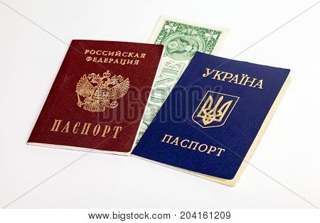 Ukrainian and Russian passports with one american dollar on the white background