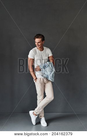 Young and handsome. Full length of handsome young man looking away and keeping hand in pocket while standing against grey background