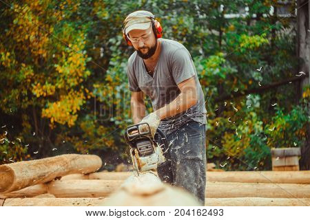 Man cutting piece of wood with chain saw.