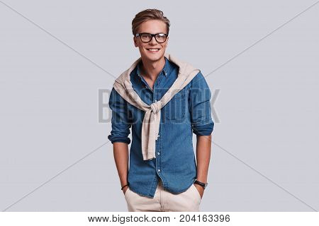 Used to look good. Handsome young man looking at camera and keeping hands in pockets while standing against grey background