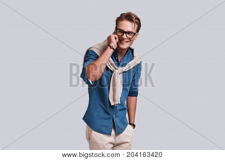 Good talk. Handsome young man talking on the smart phone and looking away with a smile while standing against grey background