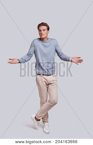 Feeling uncertain. Full length of handsome young man looking at camera and keeping arms outstretched while standing against grey background
