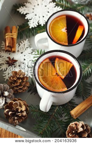 Mulled wine with spices and citrus fruit on vintage tray. Toned image