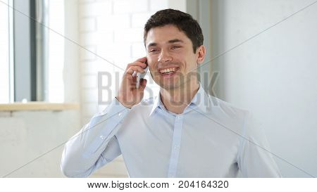 Businessman Answering Phone Call In Office At Work