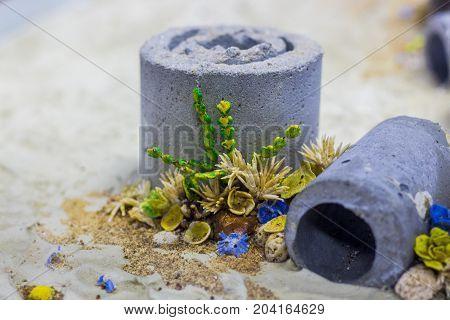 Close up of aquarium equipment in the fish tank. Concrete block and plastic flower on sand ground to decoration in the aquarium.