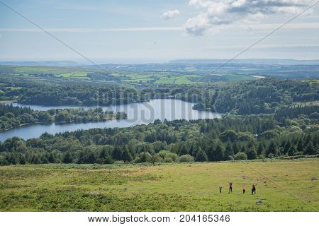 Family jumping in the landscape of Dartmoor national park with Burrator reservoir behind.