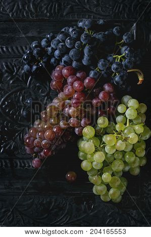 Variety of three type fresh ripe grapes dark blue, red and green. Close up over black metal ornate background. Top view