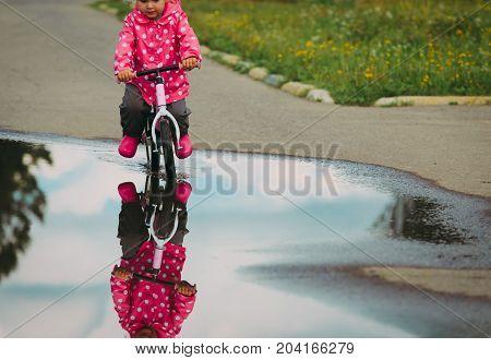 little girl riding bike in water after rain, kids outdoor activities