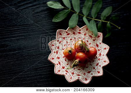 Useful antioxidant rosehip lying on a platter on a dark background. Healthy eating during deficiency