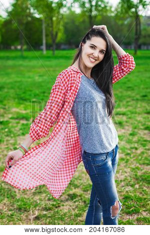 beautiful hipster teen in park. Looking at camera. Positive human emotion facial expression body language, concept of funny girl. Dressed in a gray shirt, blue jeans and a T-shirt in a red cage