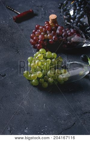 Variety of three type fresh ripe grapes dark blue, red and green in different lying wine glasses with old corkscrew over black texture background with copy space