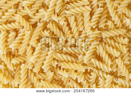 Close up of uncooked fusilli pasta background
