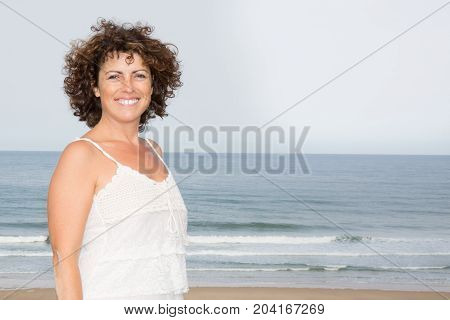 Woman Wearing A White Dress Standing On A Beach And Enjoying The Sun