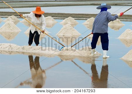 HUAHIN, THAILAND - MAY 13, 2008: Unidentified people work at the salt farm in Huahin Thailand. Salt production is one of the main industries in Huahin area it brings modest income to many local families.