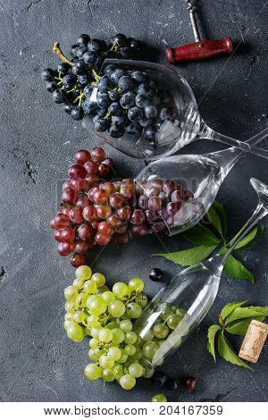 Variety of three type fresh ripe grapes dark blue, red and green in different lying wine glasses with old corkscrew over black texture background. Top view with copy space