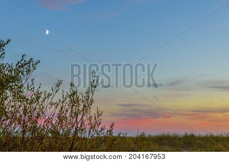 very blue sky with clouds and the moon
