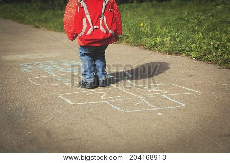little girl playing hopscotch game after school or daycare