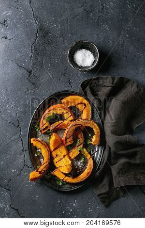 Roasted sliced pumpkin with balsamic sauce, greens and sea salt. Served on vintage metal tray with textile napkin over black texture background. Top view with space