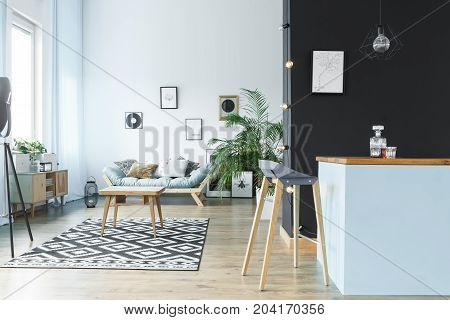 Wooden table in spacious monochromatic living room with settee and barstool at kitchen island