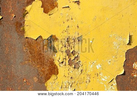 Rusty metal background surface with pealing yellow paint