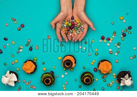 Hands With Candies And Halloween Cupcakes