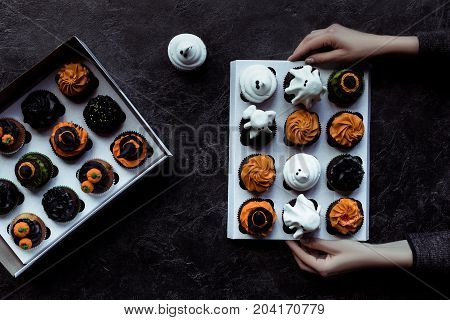 Hands Holding Halloween Cupcakes