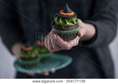 Person Holding Halloween Cupcake