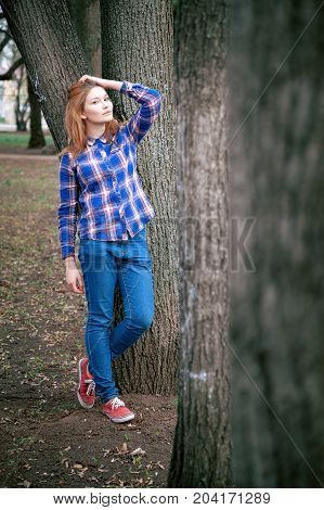Portrait of a beautiful girl. smiling, posing on camera. in a blue shirt in a cage. Against the background of the autumn park.