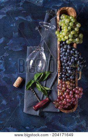 Variety of three type fresh ripe grapes dark blue, red and green in wooden bowl with empty laying wine glass, old corkscrew and green leaves over blue concrete texture background. Top view with space.