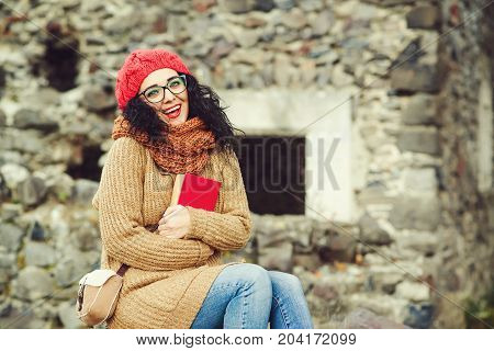 Cheerful Young Woman In Red Knitted Hat With A Book, Looking To Camera And Laughing Outdoor.