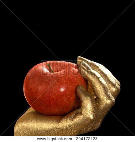 golden feminine hand holding a perfect red apple Studio shot in black back