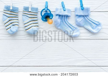 baby socks on rope at wooden background top view