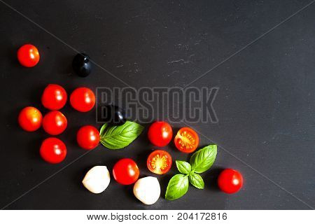 Food ingredients - Tomatoes basil leaf mozarella cheese and black olives. Fresh vegetables and fresh herbs over dark chalk board background. Healthy food diet nutrition concept.