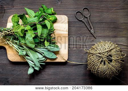 bundle of sage and thyme, mint, estragon on wooden board top view.
