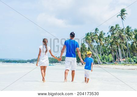 Back view of family of three - father with his child having fun at the beach