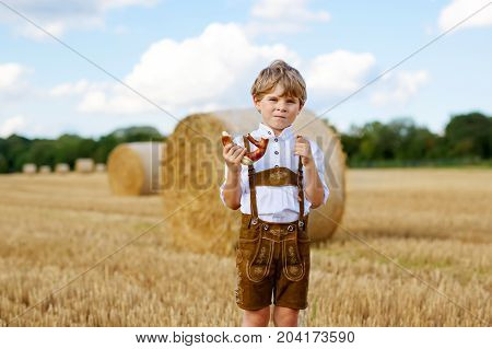 Cute little kid boy in traditional Bavarian costume in wheat field. German child with hay bale during Oktoberfest in Munich. Preschool boy play at hay bales during summer harvest time in Germany