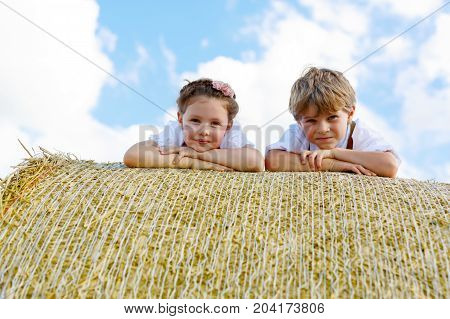 Closeup of two kids laying on hay bale in wheat field. Portrait of german children during Oktoberfest. Preschool Boy and girl play at hay bales during summer harvest time in Germany