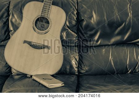 Leather journal on couch with six stringed acoustic guitar.
