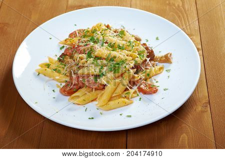 Italian Penne rigate pasta with sausage perish , close up meal