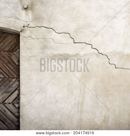 white stucco cracked wall and part of wooden door