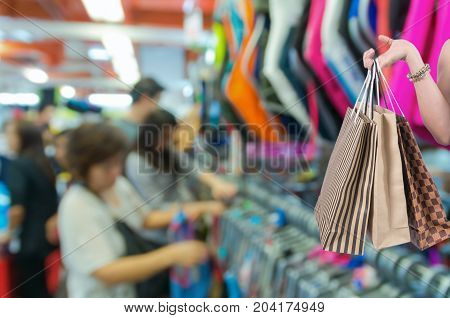 Holding shoping bags by hand on Abstract blurred photo of store blur with customer choose product bokeh background