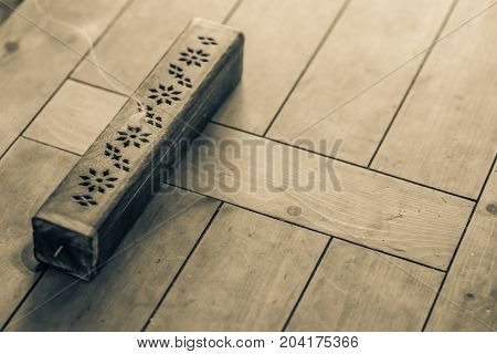 Sepia photo wooden incense burner on solid oak table.