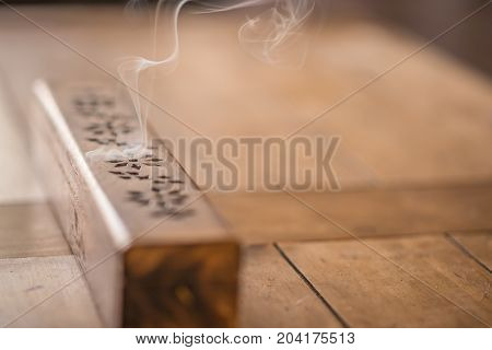 Wooden incense burner with smoke rising on a solid oak table.