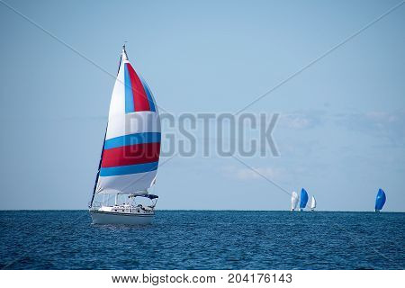 sailboats racing on Lake Michigan with colorful spinnakers