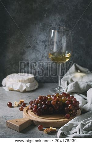 Bunch of red grapes, camembert cheese, croutons and glass of white wine served on wooden serving board over gray kitchen table with textile linen. Rustic style.